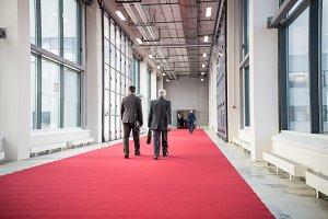 Two men walking on a red carpet