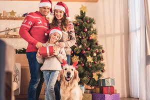 smiling family in santa hats with do