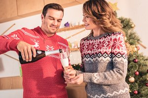 happy couple in christmas sweaters,