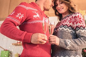 happy couple in christmas sweaters c