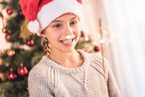 smiling preteen kid in santa hat hol