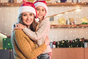smiling mother and daughter in santa
