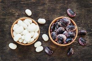 white and dark beans on a dark woode