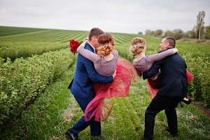 Handsome groomsmen holding bridesmai