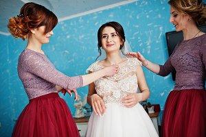 Bridesmaids helping bride to get rea