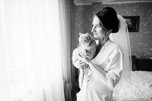 Bride posing with her cat inside her