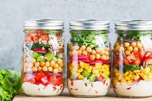 Three glass jars with layering salad