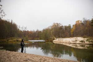 On the banks lake. Curly girl posing