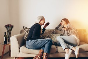 Two women sitting on couch at home