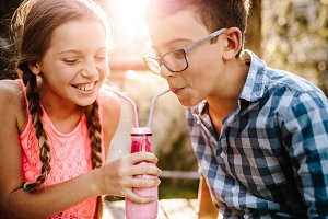 Kids drinking smoothie together