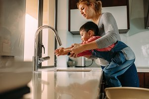 Son washing hands with mother