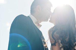 Kissing loving wedding couple on sun