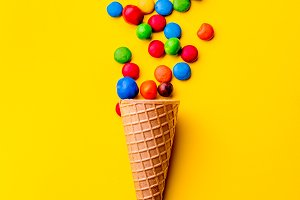 Ice creame cone with candy on yellow