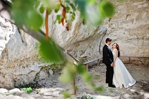 Wedding couple against cave at summe