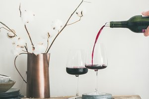 Red wine pouring from bottle in man