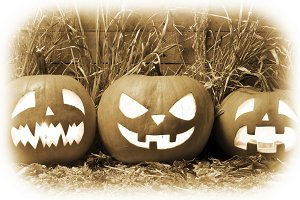Three Halloween pumpkins on black an
