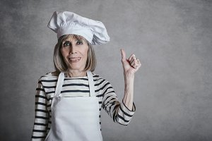 Smiling senior woman with cook hat