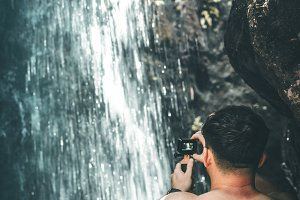 Tourist man on a waterfall