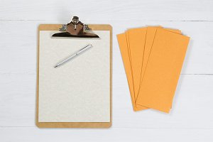 Blank clipboard with pen and envelop