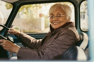Senior woman driving a car on winter
