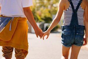 Kids in love walking on road holding