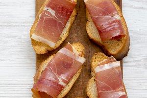 Crostini with serrano ham on wooden