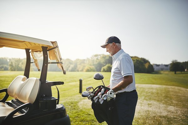 Senior man putting his golf club ba…