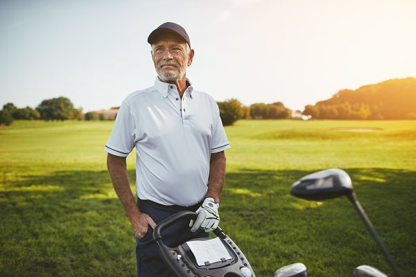 Senior man standing with his clubs…