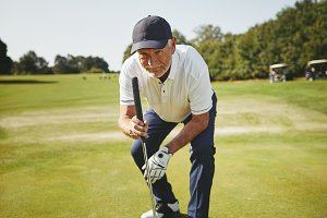 Senior golfer checking a golf green