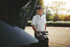 Senior man putting his golf clubs in