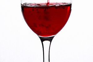 Splash of wine in a wineglass on a w