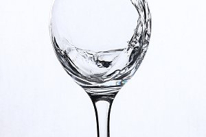 A splash of water in a wineglass on