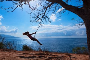 Happy girl have fun swinging high in