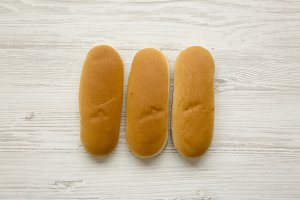 Hot dog buns on white wooden surface