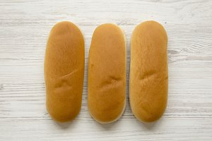 Fresh hot dog buns on white wooden