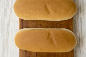 Hot dog buns on wooden board