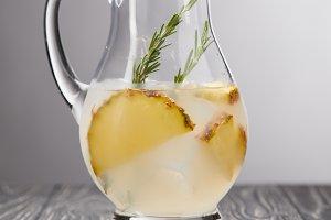 jug of lemonade with rosemary and pi