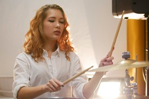 Pretty redhead girl playing drums in