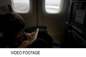 Boy using tablet PC in plane going