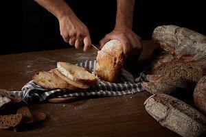 cropped shot of male baker cutting b