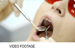 Woman being under dentists