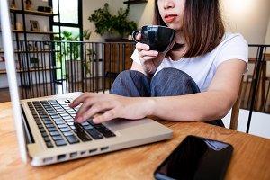Asian women relax playing laptops.