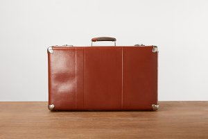 Vintage brown leather suitcase on wo