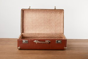 Open vintage suitcase on wooden tabl