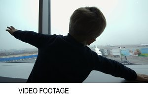 Boy looking at the plane from window