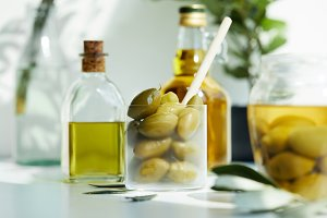 glass with spoon and green olives, j