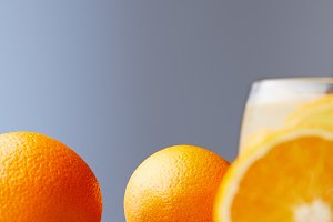 ripe oranges and glass of juice on w
