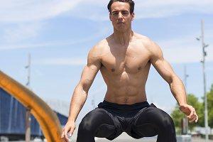 Muscular man doing box jumps outdoor