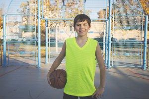 Cheerful teen holding a basketball o