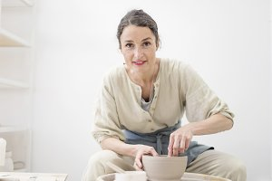 Woman hands makes clay pot on the po